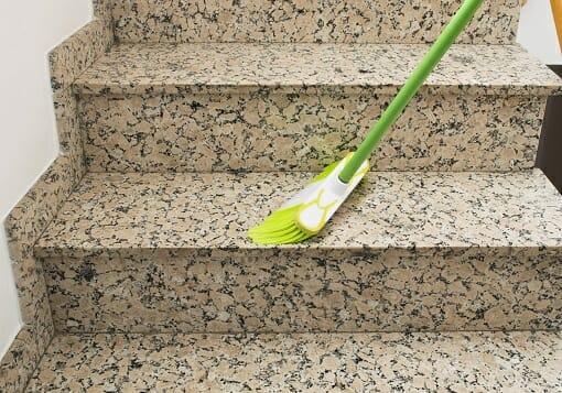 Reinigung eines Treppenhauses mit einem Besen